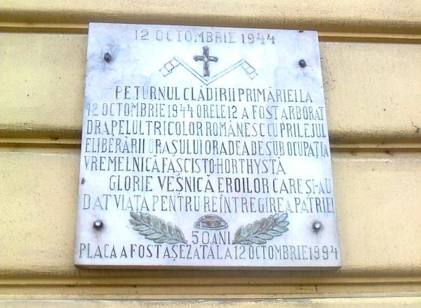 Emléktábla a nagyváradi városháza homlokzatán (Felirata: A városháza tornyára 1944. október 12-én, 12 órakor tűzték ki a román trikolórt az átmeneti horthysta-fasiszta korszak alóli felszabadulás alkalmából. Örök dicsőség a hősöknek, akik az életüket adták a haza teljessé tételéért. Az emléktábla 1994. október 12-én lett felhelyezve)