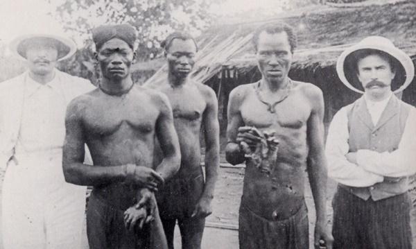 brit misszionáriusok kongói férfiak társaságában, akik az ABIR társaság milíciája által levágott kezeket mutatnak